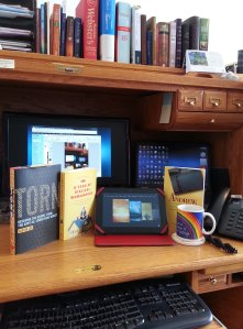3 books and kindle on desktop
