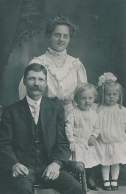 Grandma and Grandpa. The little girl scowling on the right is my mom. The happy little boy is Uncle Helmer.