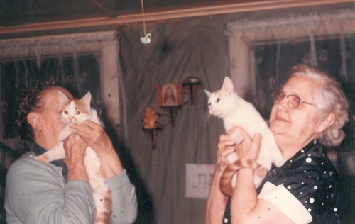 Eva and Grandma with their cats. Eva never liked to have her picture taken - that's why she's hiding behind her cat.